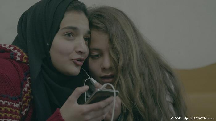 Two girls sharing earphone on a smartphone (photo: DOK Leipzig 2020/Children).