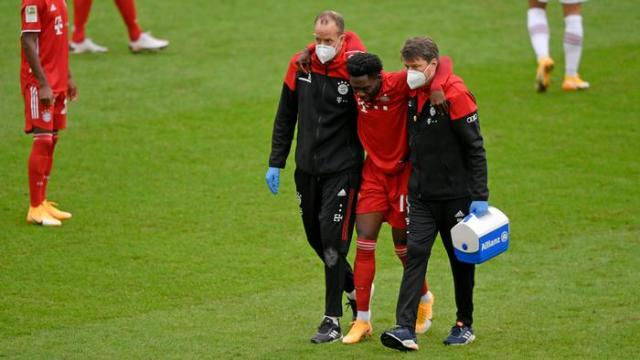 Bayern Munich's Alphonso Davies is helped off the field injured in October