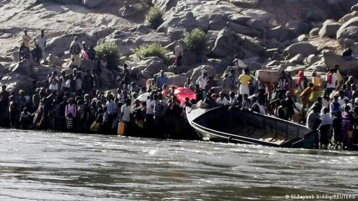Refugees wait to cross a river to escape fighting