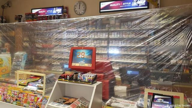 A kiosk with plastic wrap hanging in front of the cash register