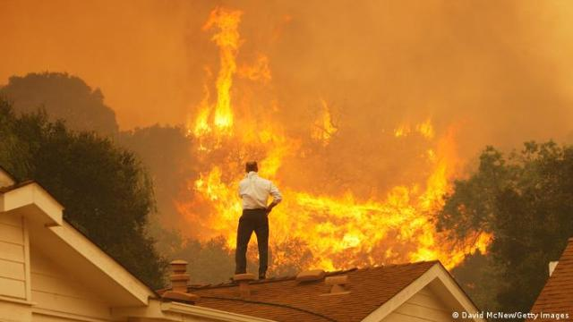 A man stands on his roof as a bushfire burns in Calfornia