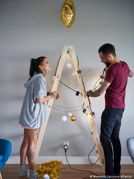 Modern couple decorating the home at Christmas time using ladder as Christmas tree