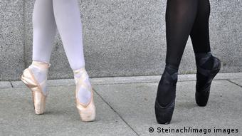 One ballerina wearing white tights and pink shoes, another wearing black tights and shoes