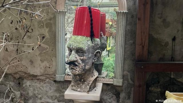 The bust of a man with a fake mustache and fez-style hat made of a bucket