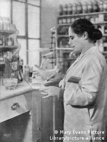 Helena Rubinstein in a laboratory setting, surrounded by vials on a workbench and shelves