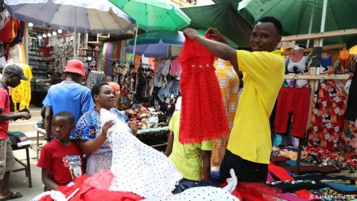 A man holds up a dress for a buyer at a market in Tanzania