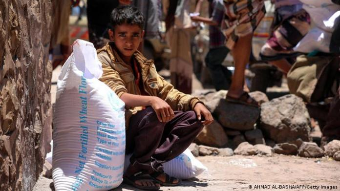 A Yemeni boy receives humanitarian aid, donated by the World Food Programme (WFP), in the country's third city of Taez