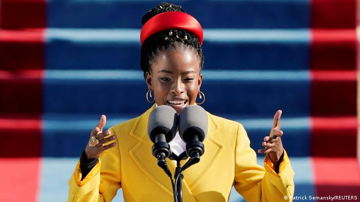 Poet Amanda Gorman at the Biden-Harris inauguration in January 2021: at the microphone, wearing a yellow jacket and a red headband, gesticulating.