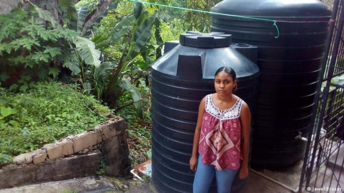 A neighbor of Noreen Nunez in the St. Augustine neighborhood of Trinidad stands next to her water tanks