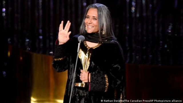 Deepa Mehta, a woman stands on stage at a microphone