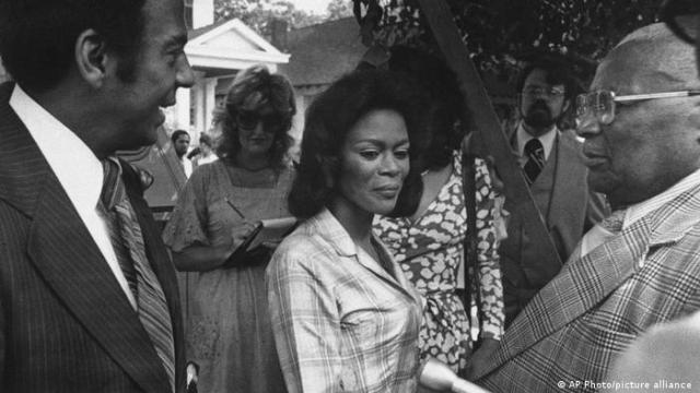 A black and white photo from a film set, Cicely Tyson stands between two men