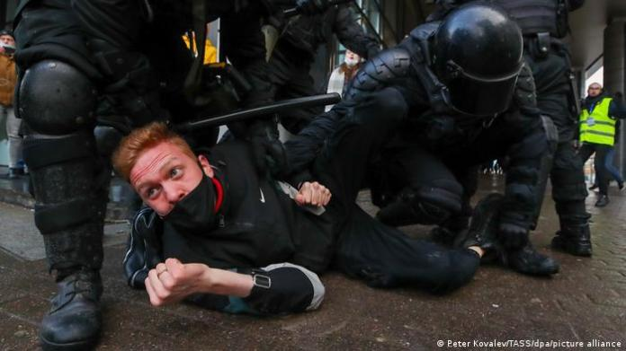 Riot police officers detain a demonstrator during an unauthorised protest in support of the detained opposition activist Alexei Navalny.