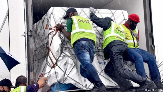 Workers unload the first shipment of Corona vaccine that arrived in South Africa