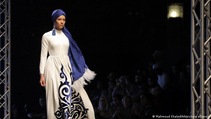 In Dubai, a model presented a creation by Muslima Wear, a white dress with a blue pattern, at the Dubai Modest Fashion Show 2017.