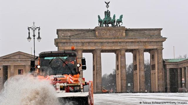 Brandenburg gate gets a cleaning during heavy snowfall.