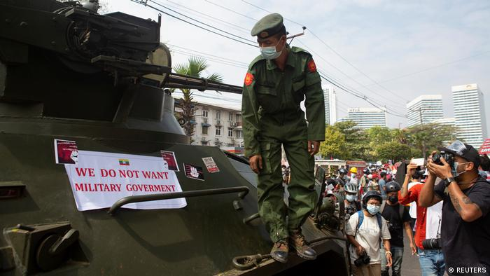 A soldier looks at a protest banner attached to a military vehicle