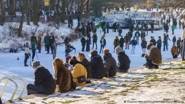 Some people sit on a wall while others walk along a frozen canal in Berlin
