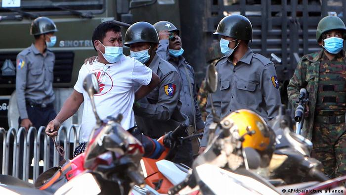 Police arresting a man during protests in Mandalay