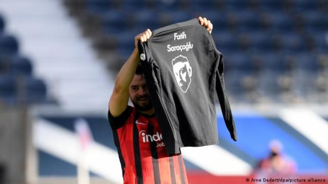 Eintracht Frankfurt's Amin Younes holds aloft the image of Fastih Sarancoglu, one of the victims of the Hanau terrorist attack a year ago