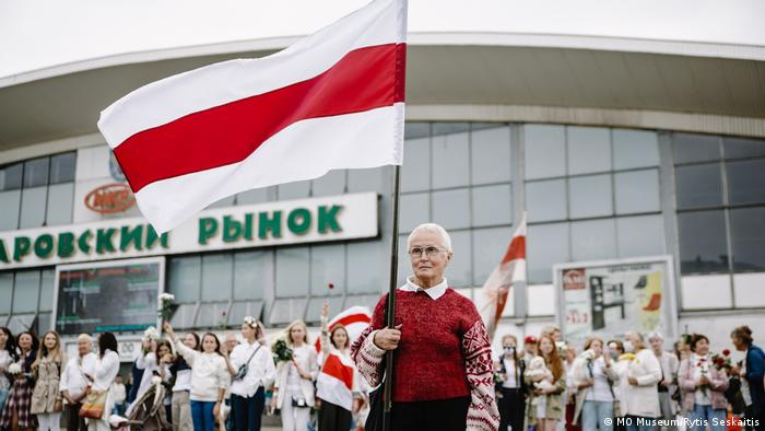 This photo shows an elderly woman in a red pullover holding the Belarussian flag. The picture was taken by Viyaleta Sauchyts.