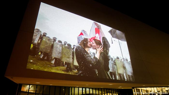 This image shows a photograph projected on the outer walls of the MO museum. The photograph shows two women protesters kissing under the Belarusian flag.