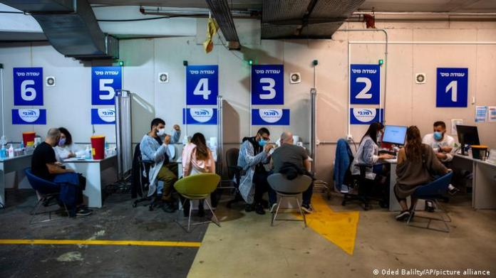 Israelis receive Pfizer-BioNTech COVID-19 vaccine from medical professionals at a coronavirus vaccination center.