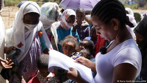 An aid worker distributes food and other items in Mekele, Tigray