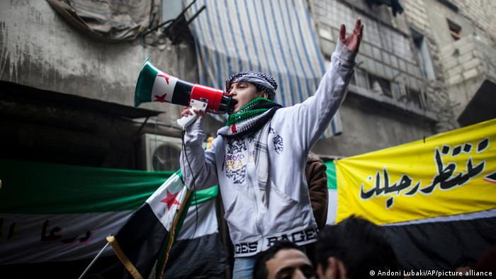 A child uses a megaphone to lead others in chanting anti-government slogans during a demonstration in Aleppo