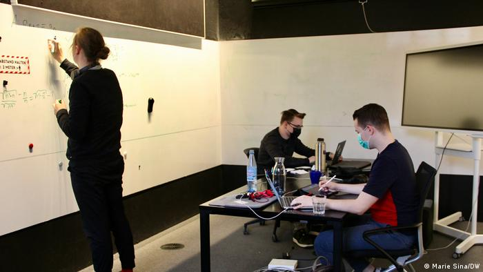 Three men are working at a desk and a whiteboard in the Digital Church