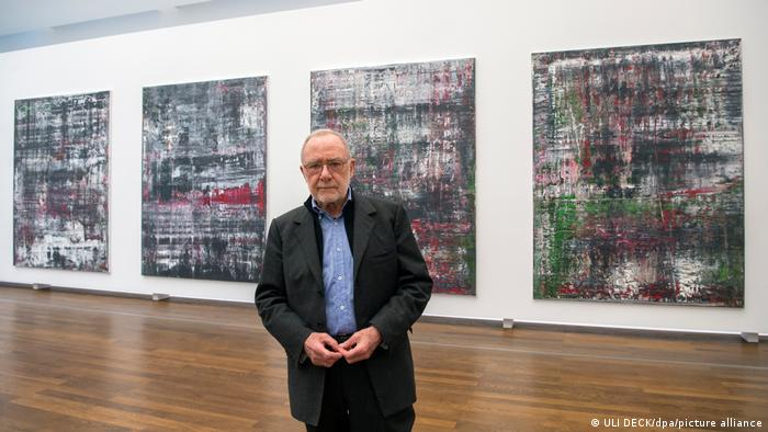 An elderly man stands in front of four abstract paintings