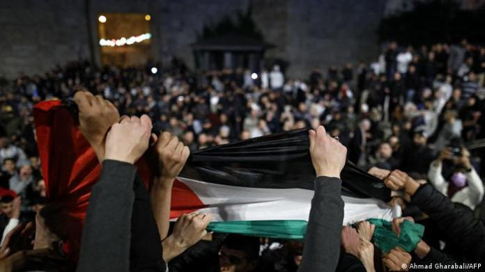 Palestinian protesters wave the national flag outside the Damascus Gate in Jerusalem's Old City.