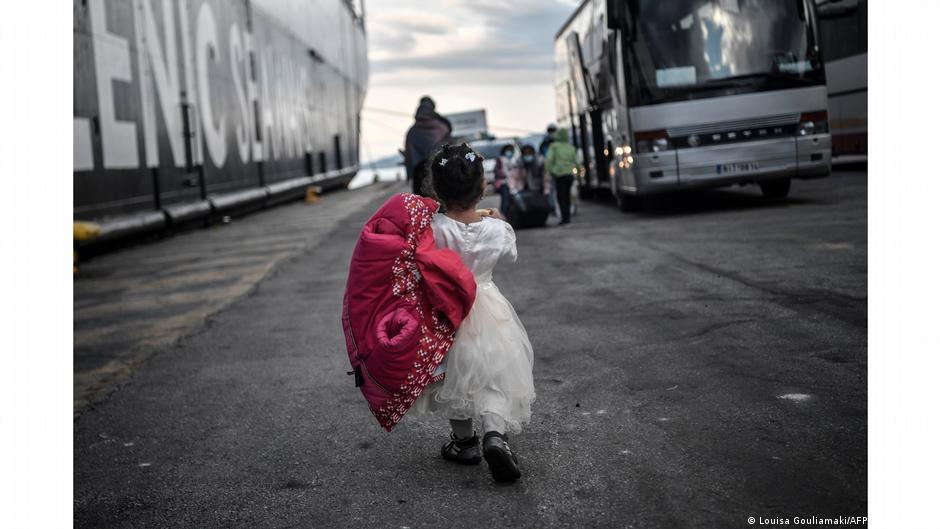 Little girl seen from back walking to a bus at a port. Photo:Louisa Gouliamaki, Lesbos, Greece