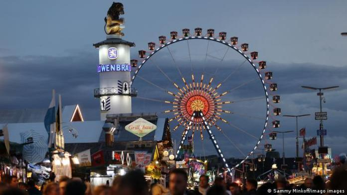 Evening view of the Oktoberfest festival with beer people mingling among beer tents and ferris wheel