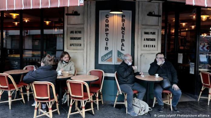 Guests in front of a reopened café in Paris, France