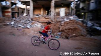 Boy riding bicycle by Gazan camp and the rubble of their homes in May 2021.