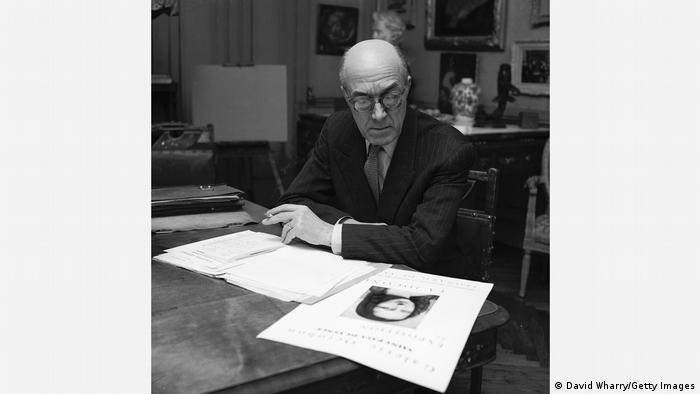 Raymond Hekking, man seated at desk looks at printout of painting