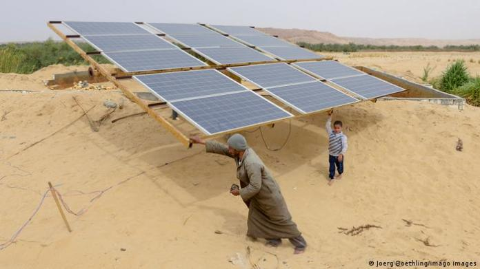 A man and his child in front of the solar panels in the desert