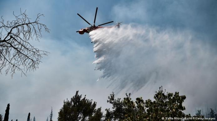 A helicopter drops water on a forest fire