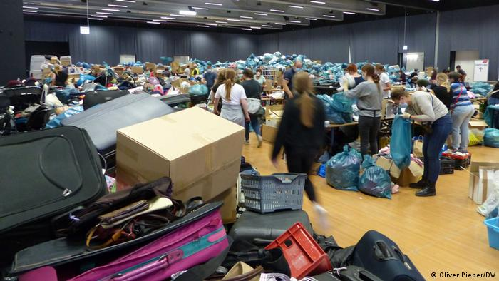 A large room filled with people, boxes and bags