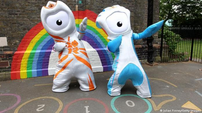 Wenlock (l.) and Mandeville (r.) two upright lumpy creatures with one eye in the middle of their faces stand in front of a wall with a rainbow