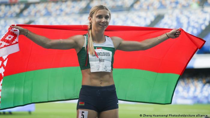 Krystsina Tsimanouskaya holding the Berlarusian flag