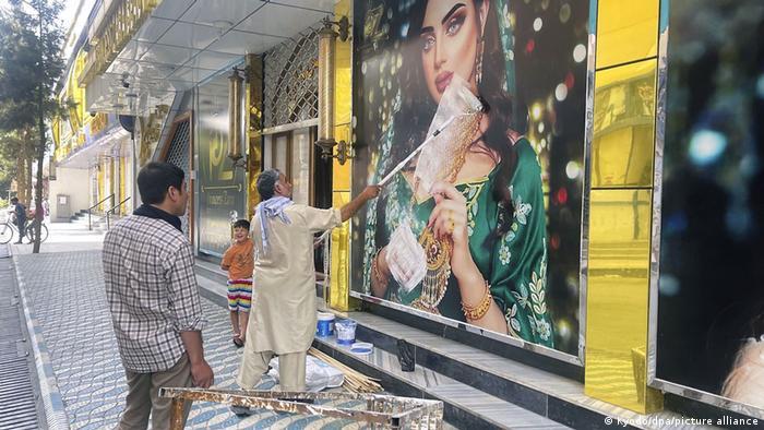 Власники крамниць у Кабулі спішно замальовують зображення жінок