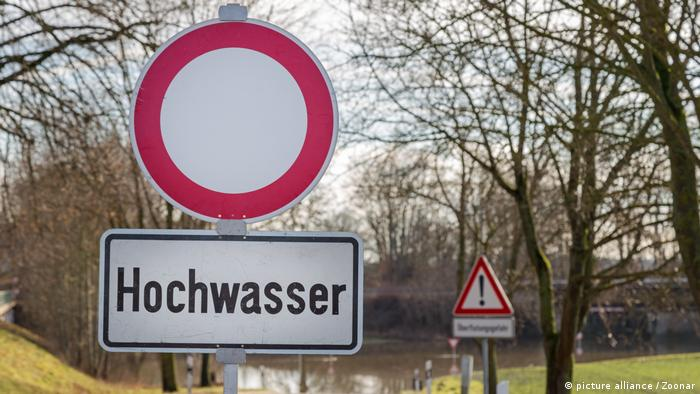 A sign that says high water in German in front of a body of water.