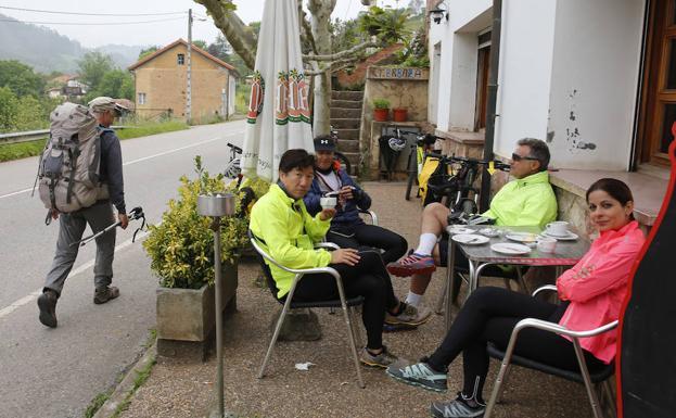 Un grupo de ciclistas brasileños descansa al comienzo de la etapa mientras pasa un caminante por La Bolguina. / DAMIÁN ARIENZA