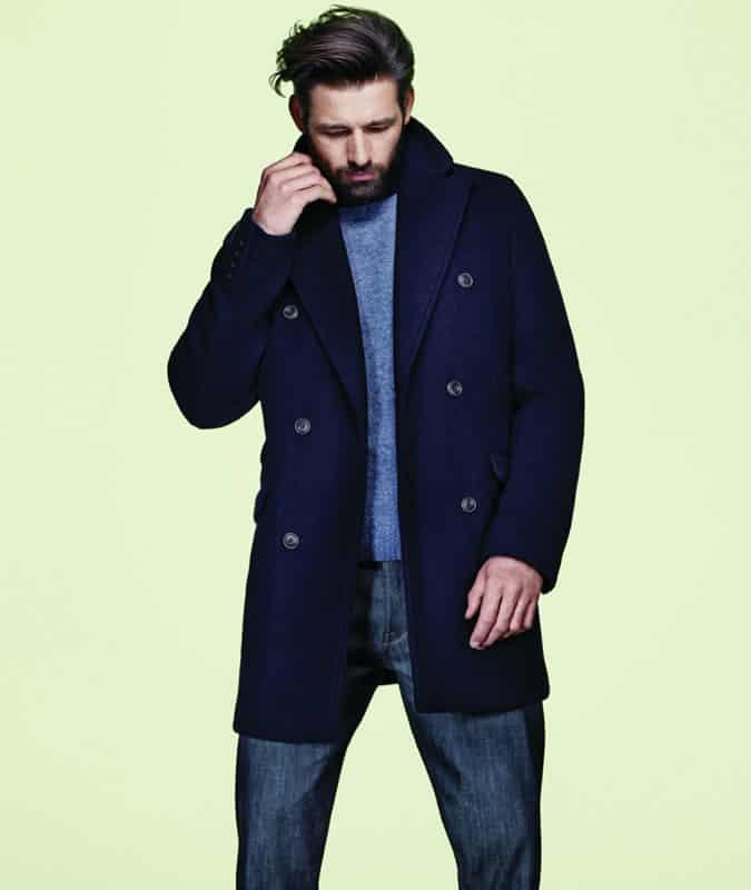 Homme portant un caban, un pull en cachemire et un jean foncé