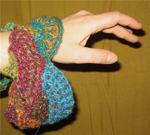 Poignet de tricot ample multicolore sur un poignet avec une main - Multicolor large knitted cuff on a wrist and hand