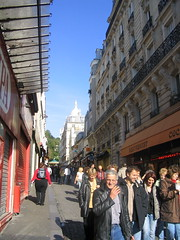 Image of a street with people and Sacré Cœur in the distance