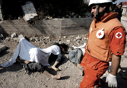 Red Cross member passes dead bodies Qana Lebanon 30 Jul 2006