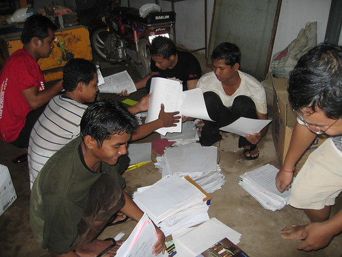 volunteers arranging the paper of different types so that it's easy to sell