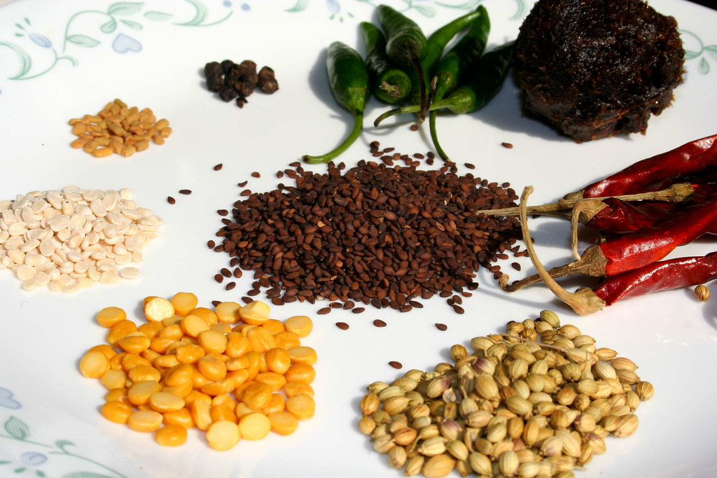 From Top Clockwise: Green Chillies, Tamarind, Dry Red Chillies, Coriander Seeds, Channa Dal, Urad Dal, Fenugreek Seeds, Pepper. In the Center: Sesame Seeds